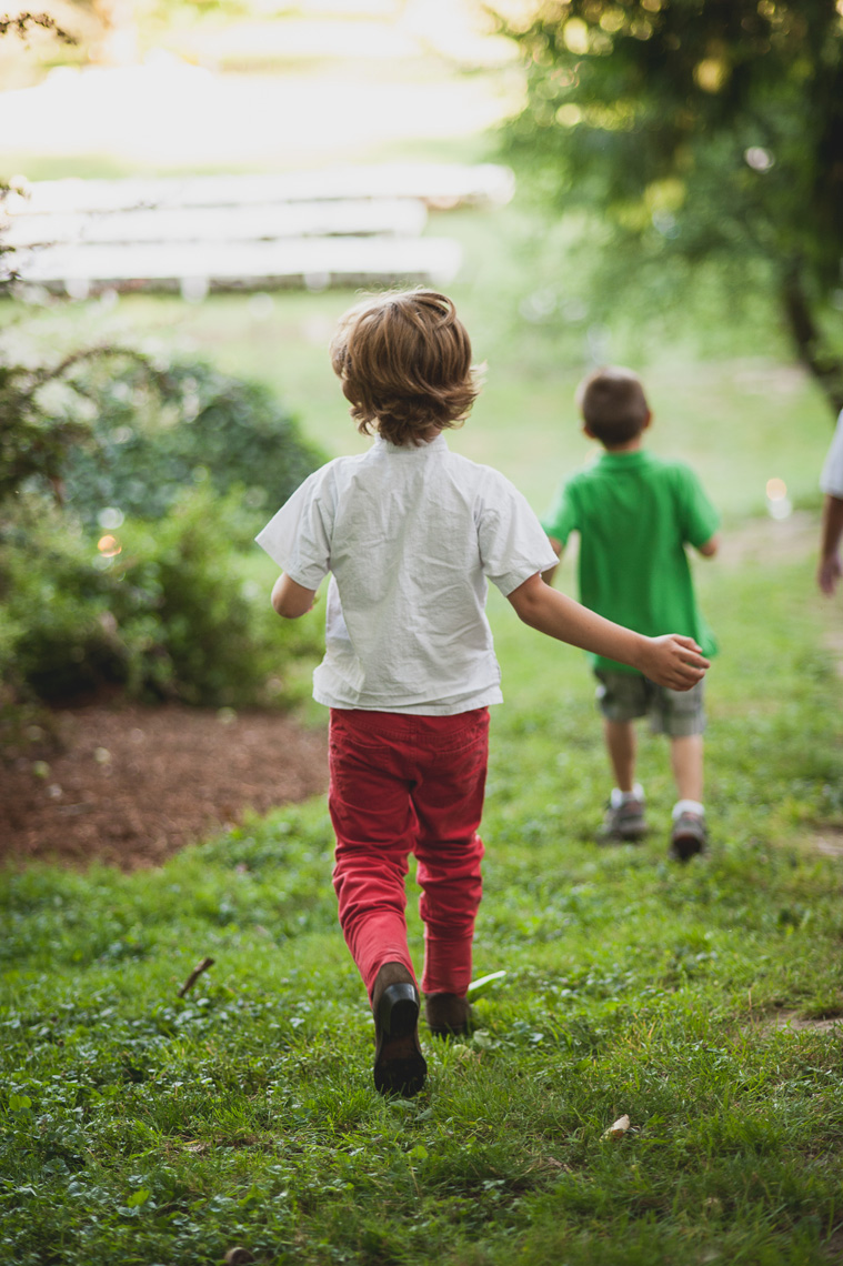 A kid runs down a grassy hill in this lifestyle photo by Leah Verwey.