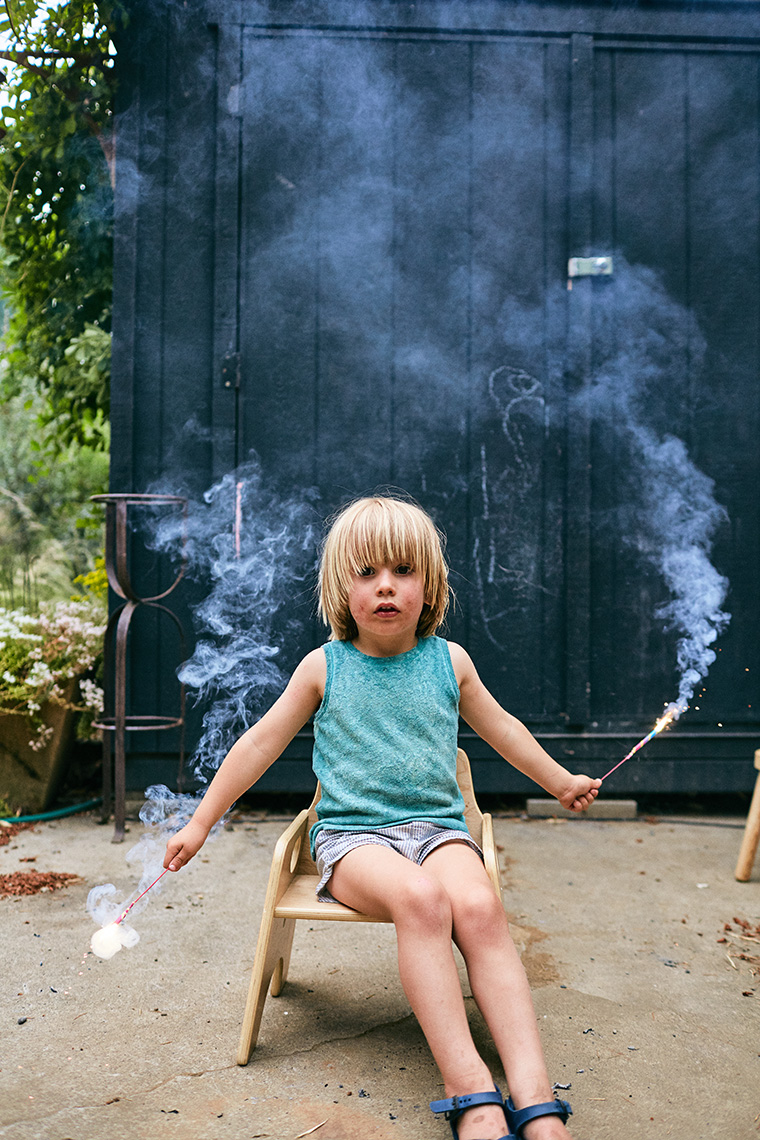 A young kiddo holds sparklers with a mute expression. Image by Leah Verwey