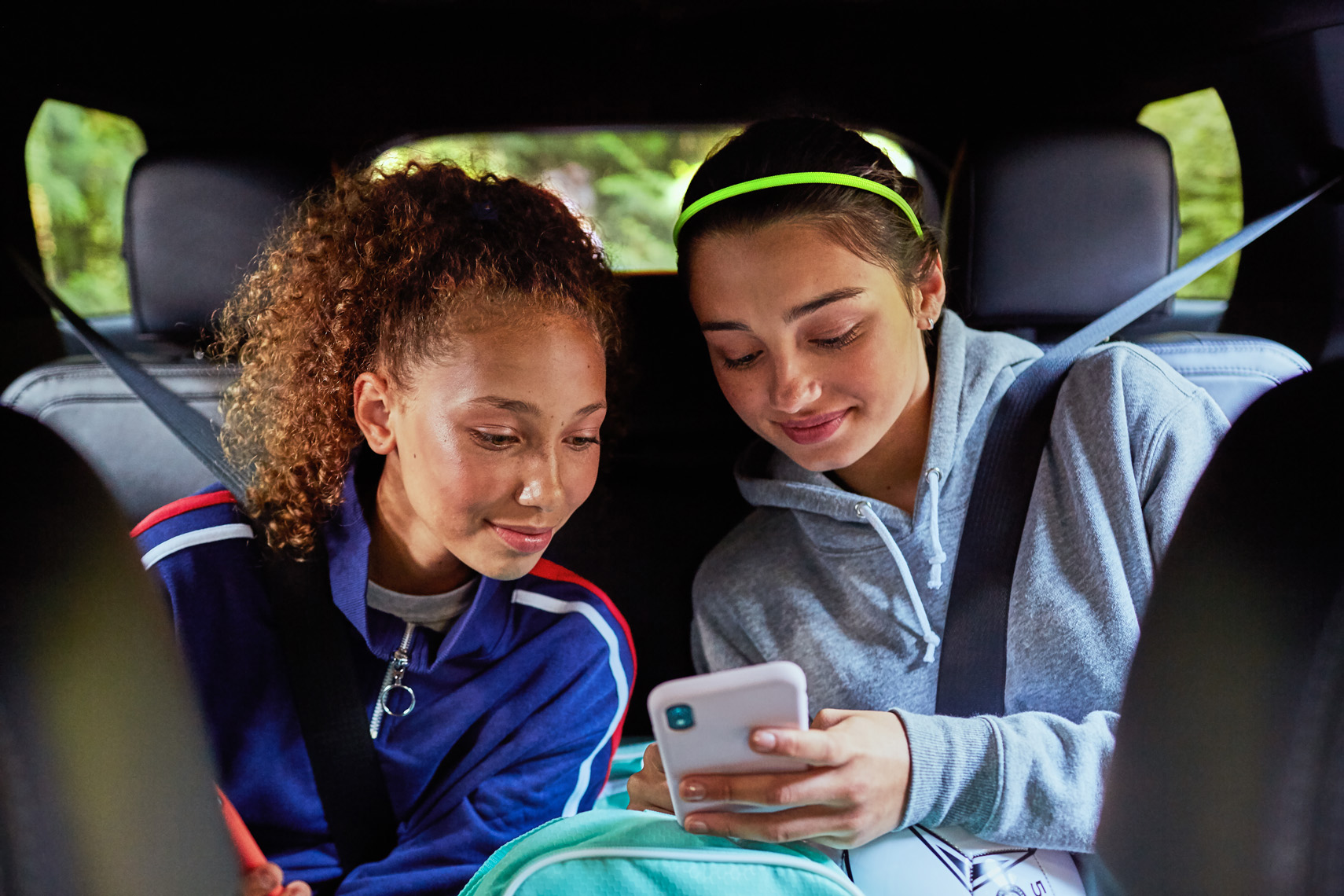 Teenage girls watch a video on a phone in the car. Lifestyle image by Leah Verwey