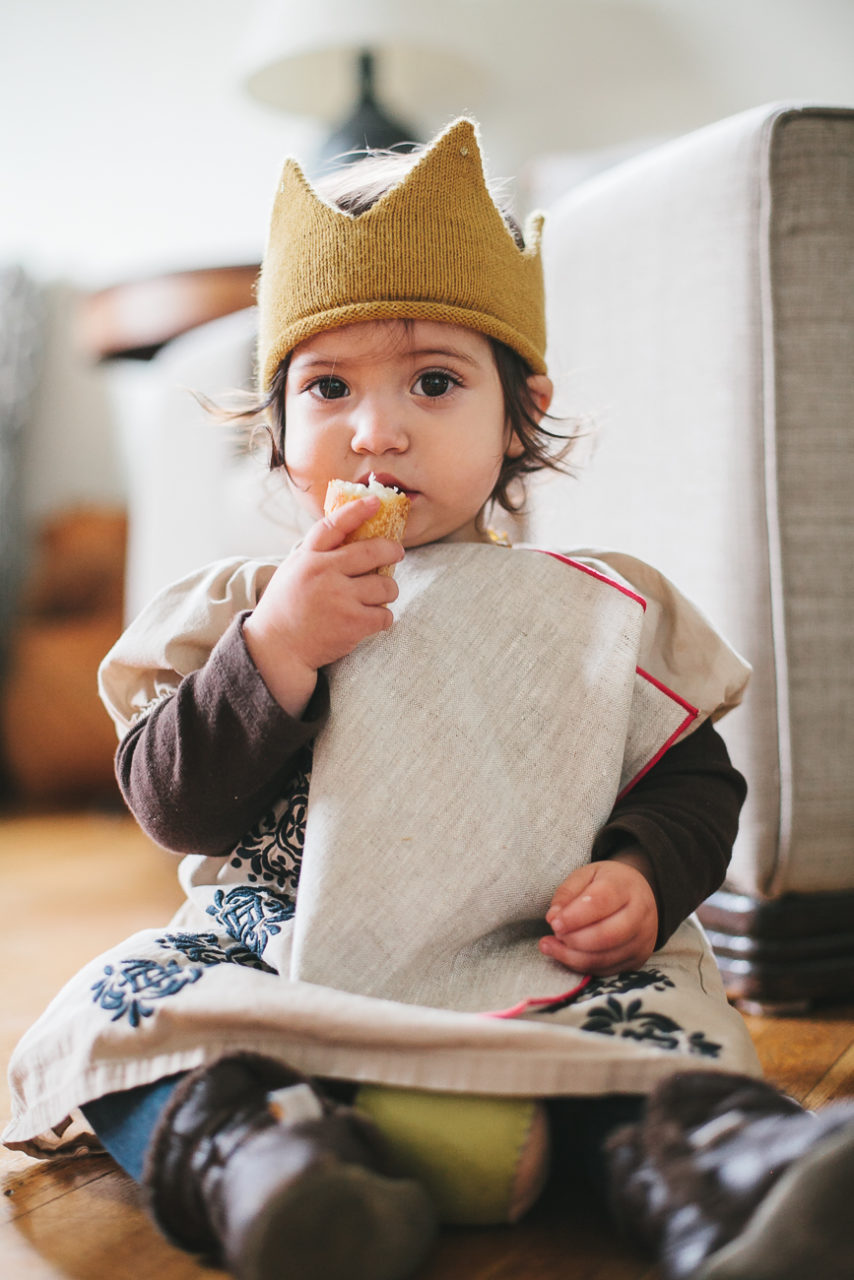 A toddler in a crown eats some bread.