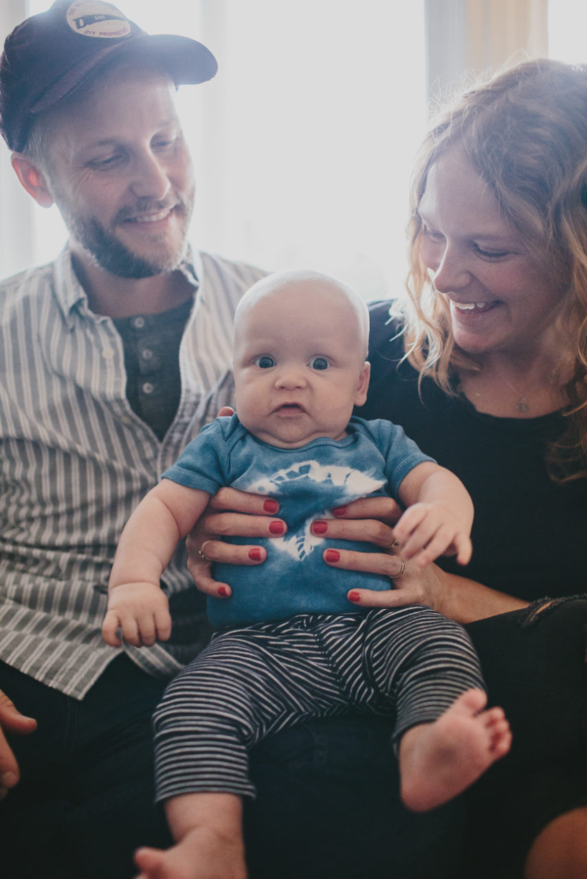 New parents snuggle their new babe in a documentary style photo - Leah Verwey