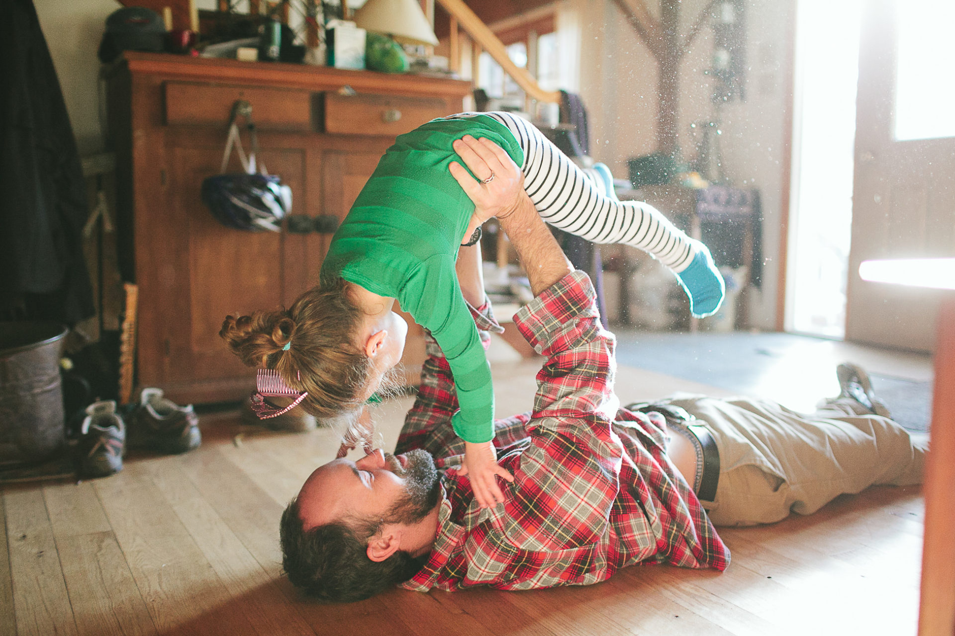 A dad plays airplane with his kid in a lifestyle photo