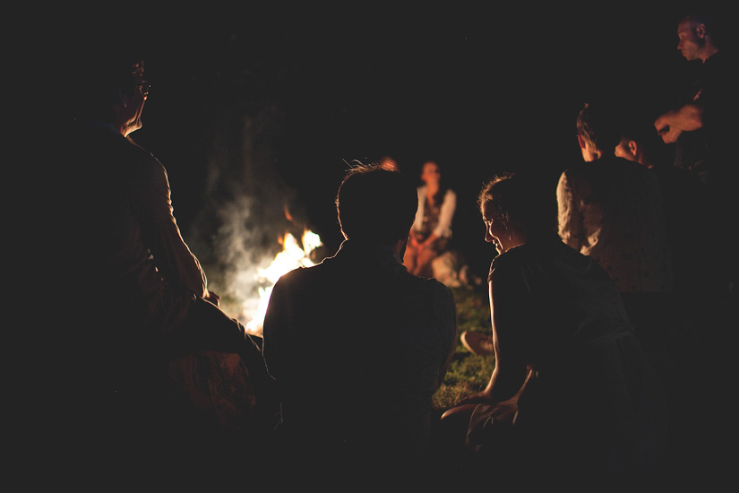 A group of people hover around a campfire - Image by Leah Verwey