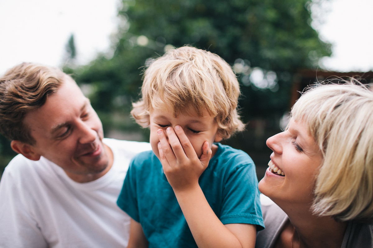 A young kid laugh with his parents in a lifestyle image by Leah Verwey