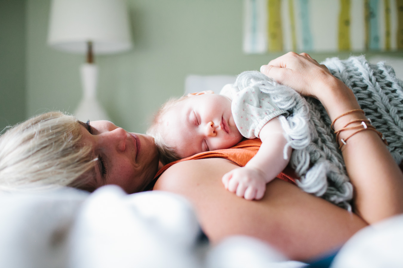 A mom cuddles her baby in bed, photo by Leah Verwey.