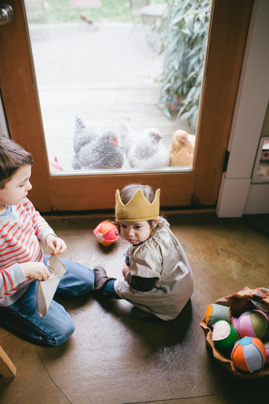 Two young kids look at back yard chickens in Portland, Oregon.